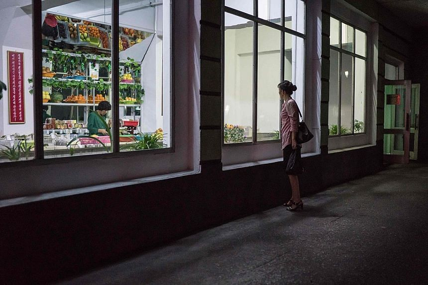 A 2017 photo of a woman outside a grocery store in Pyongyang. Natural disasters and inefficient agriculture in North Korea contributed to a plunge in food production last year, the UN says.