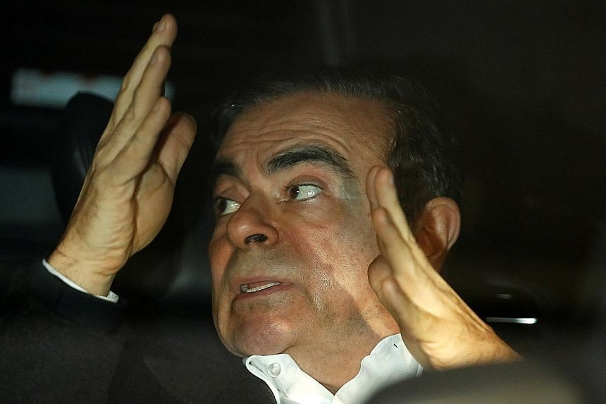 Carlos Ghosn inside a car after leaving his lawyer's office yesterday. The ousted Nissan chairman had earlier in the day left Tokyo Detention House in disguise to evade the press, after spending more than three months in custody.