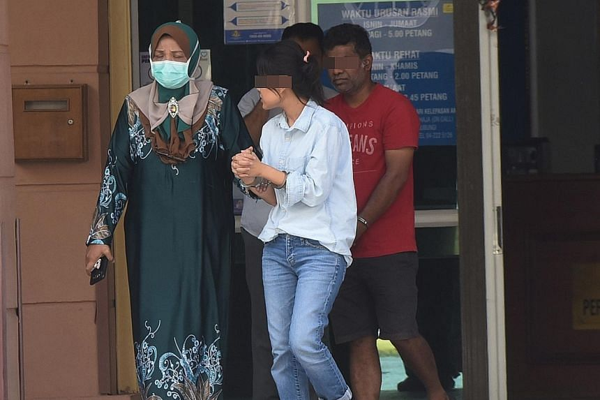 """Two handcuffed suspects in the murder of an IT manager being led out of the Penang Hospital mortuary on Tuesday. The police are also hunting a """"fair-skinned foreign man"""". The three people were seen entering a condominium with the victim - Mr Brian Pa"""