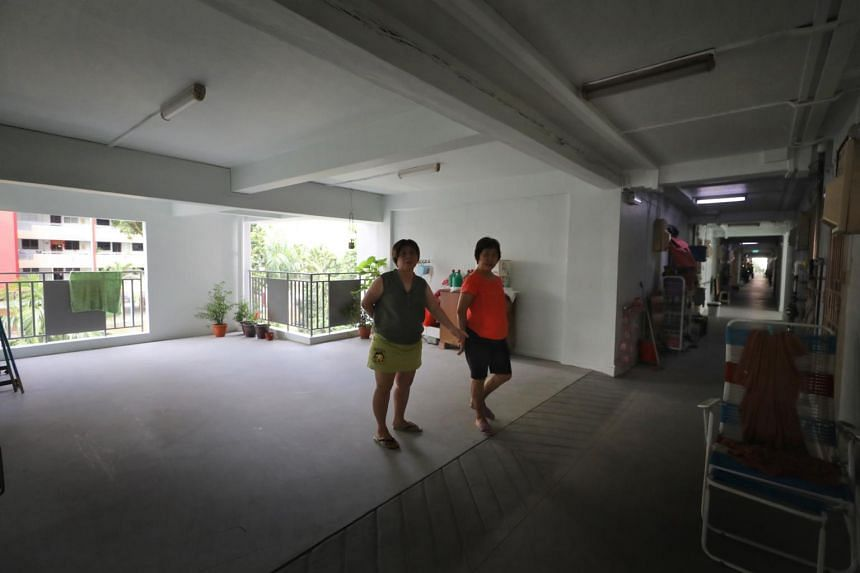 Neighbours Teo Geok Lan, 61, (right) and Leong Lye Chan, 57, at an empty area where a one-room unit used to be on the fifth floor at Block 217 Ang Mo Kio Avenue 1. The new open space allows more light and air to enter the corridor.