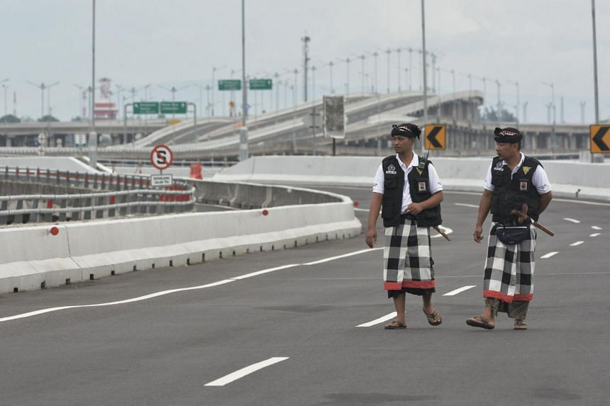Balinese traditional security guards called 'Pecalang' walk as they patrol an empty highway during Nyepi, the holy day of Silence, in Bali, on March 7, 2019.