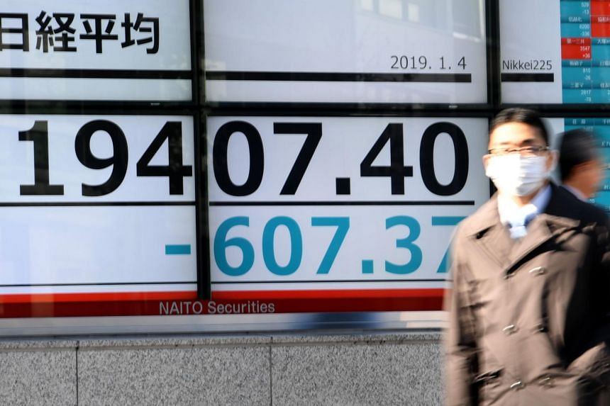 A pedestrian walks past an electronics stock indicator outside a securities company in Tokyo, on Jan 4, 2019.