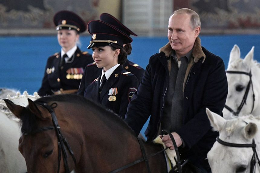 Putin rides a horse as he visits a mounted police regiment ahead of International Women's Day.