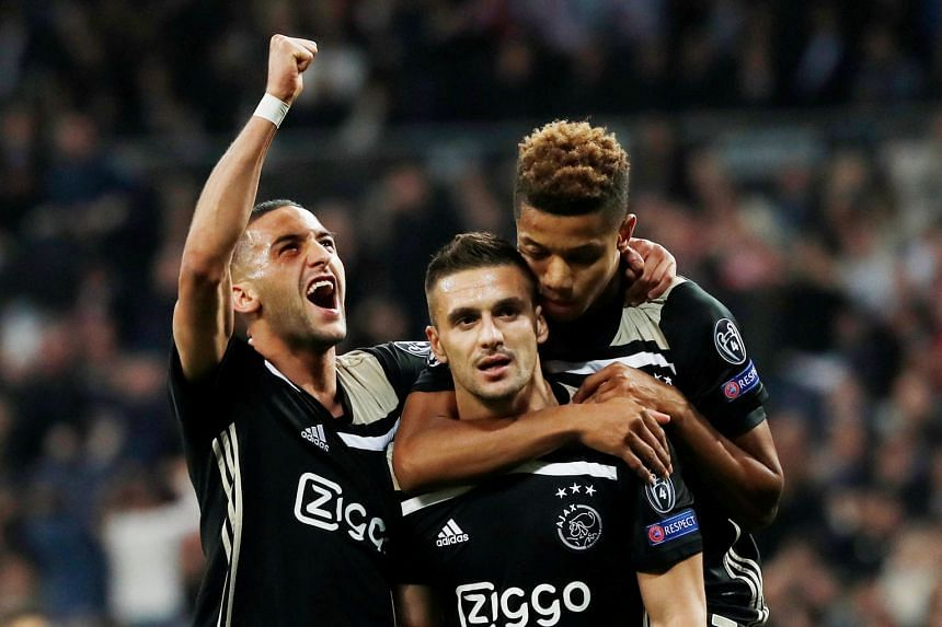 Real Madrid goalkeeper Thibaut Courtois grasping at thin air as a left-wing free kick from Lasse Schone soars past him into the top corner for Ajax's fourth goal at the Santiago Bernabeu. Dusan Tadic (centre) celebrates scoring their third goal with