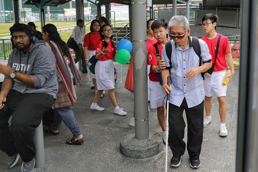 Chung Cheng High School (Yishun) students, wearing white wristbands, helping an elderly commuter at Khatib station yesterday. They also distributed balloons to commuters at MRT stations and bus interchanges.