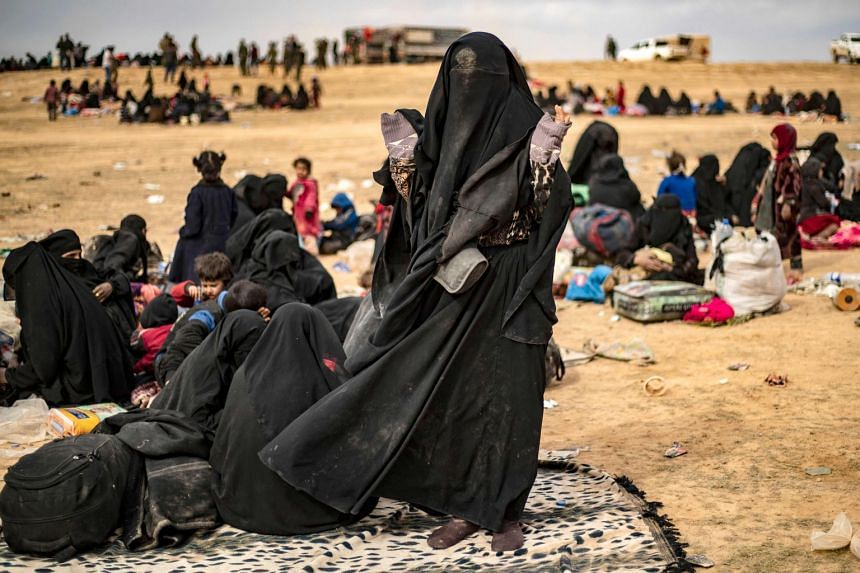 Civilians who streamed out of the ISIS' last Syrian stronghold walk towards a screening point for new arrivals run by US-backed Syrian Democratic Forces.