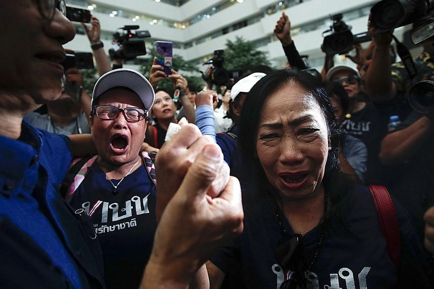 Supporters breaking into tears after Thailand's Constitutional Court ordered the dissolution of the Thai Raksa Chart Party in Bangkok yesterday.