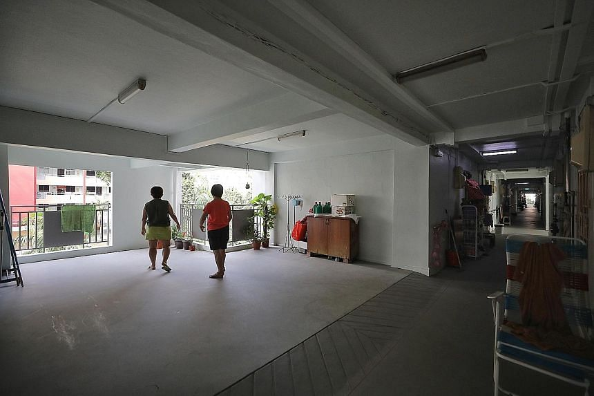 Neighbours Teo Geok Lan (right), 61, and Leong Lye Chan, 57, socialise at an open space where a one-room unit used to be on the fifth floor of their block. The corridors are now brighter and more airy, says Madam Leong.