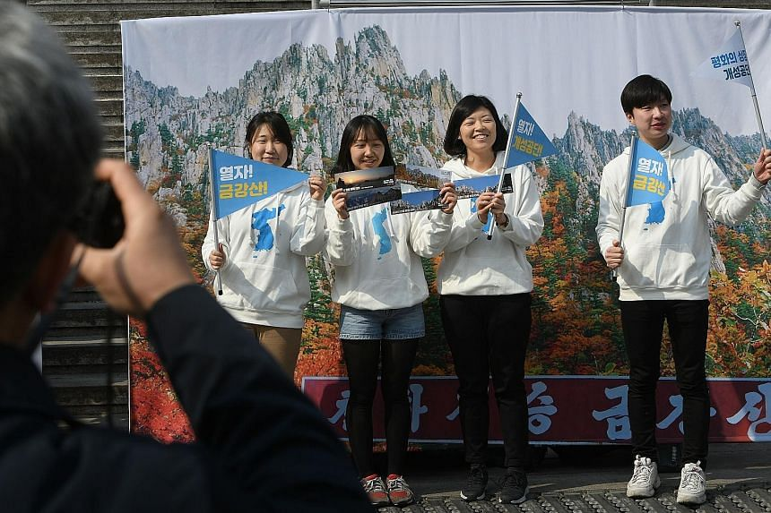 South Korean pro-unification activists in front of a banner showing North Korea's Mount Kumgang during a rally in Seoul yesterday. They were demanding the resumption of Mount Kumgang tours and the reopening of the Kaesong Industrial Complex in the No