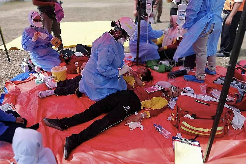 Students receiving emergency treatment after fainting from inhaling what is believed to be hazardous gas. The fumes are suspected to have come from chemical waste that was illegally dumped into a river in Johor Baru.