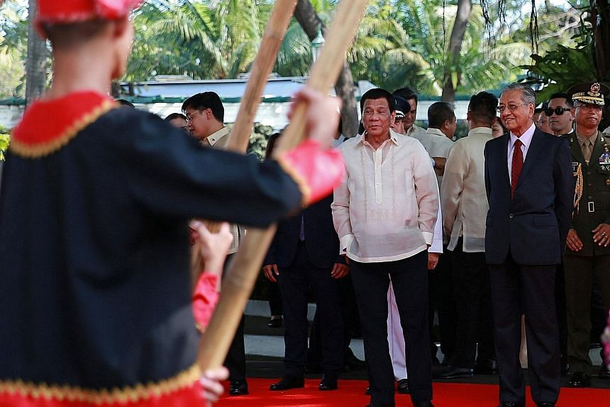 Philippine President Rodrigo Duterte (centre) and Malaysian Prime Minister Mahathir Mohamad watching a welcome dance performance at Malacanang presidential palace in Manila yesterday.