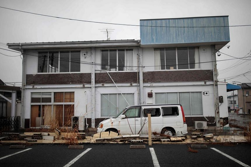 An abandoned car and house in Namie town, Fukushima prefecture on March 5, 2018.
