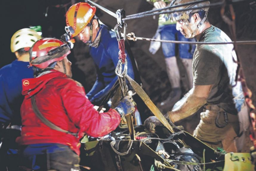 People holding an evacuated boy during the rescue operations for the youth soccer team and their coach inside a cave complex at Tham Luang cave in Khun Nam Nang Non Forest Park, Chiang Rai province, Thailand.