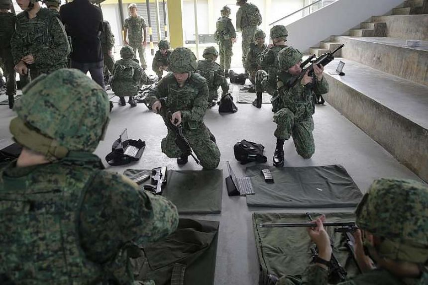Recruits undergoing weapon-handling practice at the SAF Basic Military Training Centre on Pulau Tekong.