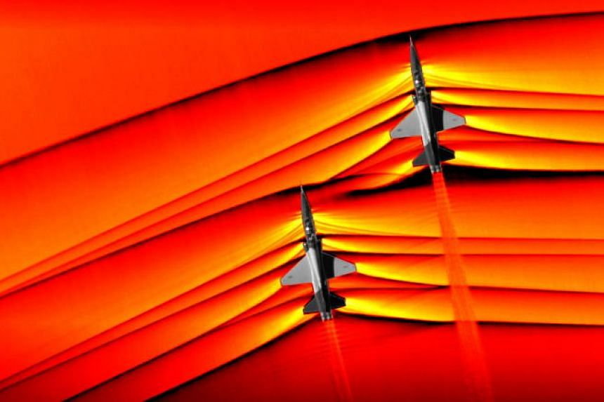 In an intricate manoeuvre by pilots at Nasa's Armstrong Flight Research Center in California, two supersonic T-38 jets flew below another plane waiting to photograph them with an advanced, high-speed camera.