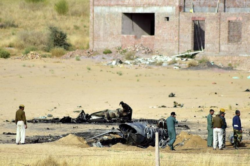 Indian policemen and officials stand near the remains of an Indian Air Force MiG-21 fighter jet after it crashed near Bikaner's Shoba Sar ki Dhani area in the Indian state of Rajasthan on March 8, 2019.