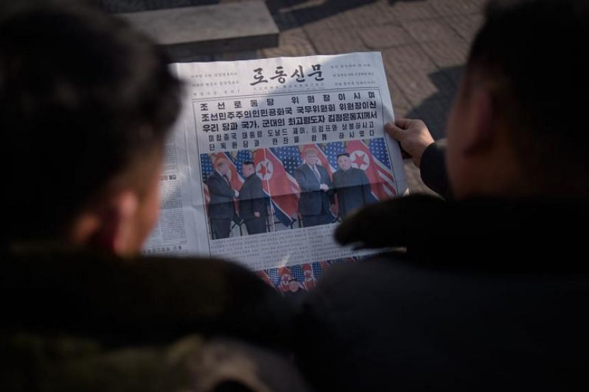 People in Pyongyang read the Rodong Sinmun newspaper that carried a front-page picture showing North Korea's leader Kim Jong Un shaking hands with US President Donald Trump during a summit in Hanoi on Feb 28, 2019.