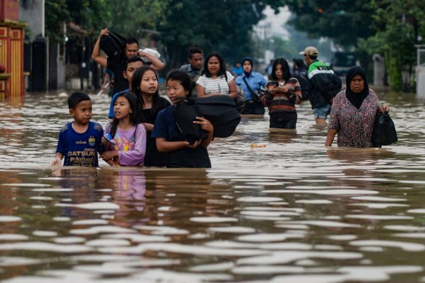 Residents in a dozen communities on the outskirts of Bandung city, east of the capital Jakarta, were forced to wade through streets filled with chest-high water in places.