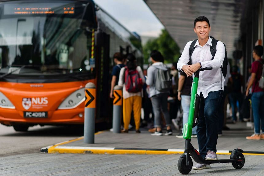 An NUS student poses on his GrabWheels scooter