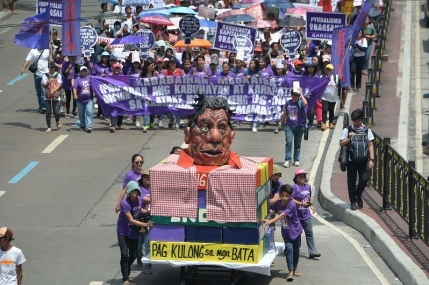 "Protesters marching on Malacanang presidential palace and chanting against President Rodrigo Duterte on March 8, 2019. Mr Duterte has repeatedly made jokes about rape and said last year that when he was a teen he indecently ""touched"" the family maid."