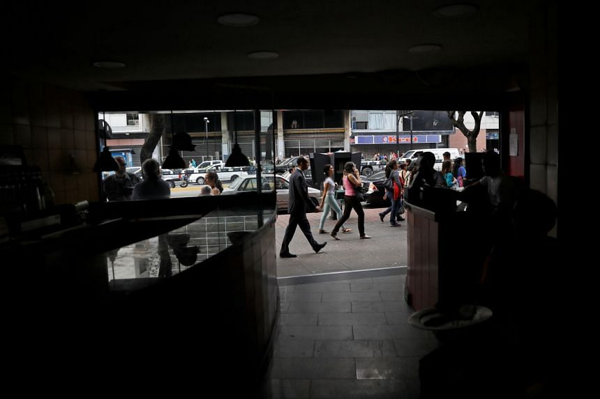 People walking in front of a restaurant during a blackout in Caracas, Venezuela, on March 7, 2019.