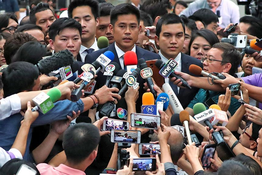 Thai Raksa Chart party leader Preechapol Pongpanit, accompanied by members of his party, speaking to the media after the verdict was handed down by the Constitutional Court yesterday.