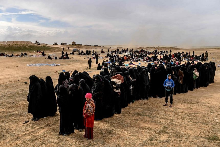 Civilians evacuated from ISIS' embattled holdout of Baghouz wait at a screening area held by the US-backed Kurdish-led Syrian Democratic Forces.