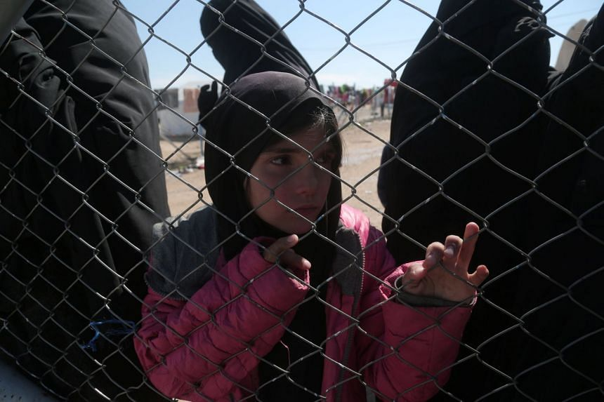 A girl looks through a chain linked fence at al-Hol displacement camp.
