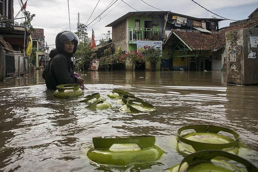 A deliveryman hauling cylinders of liquefied petroleum gas had to wade through murky floodwaters in Bojong Asih, in the Indonesian city of Bandung, as he went on his rounds yesterday. Residents on the outskirts of Bandung have been forced to walk in