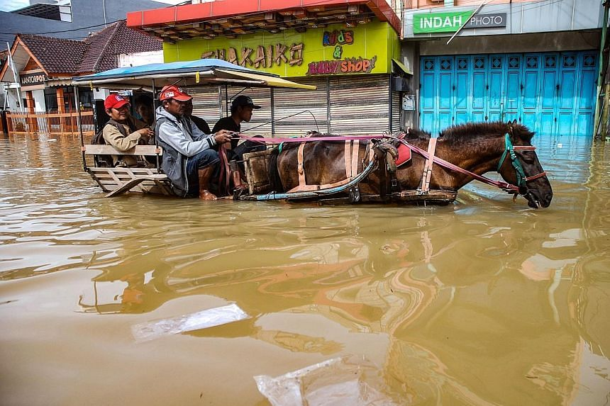 Residents making their way via horse cart along a flooded road in a Bandung village on Thursday as rain hammered West Java.