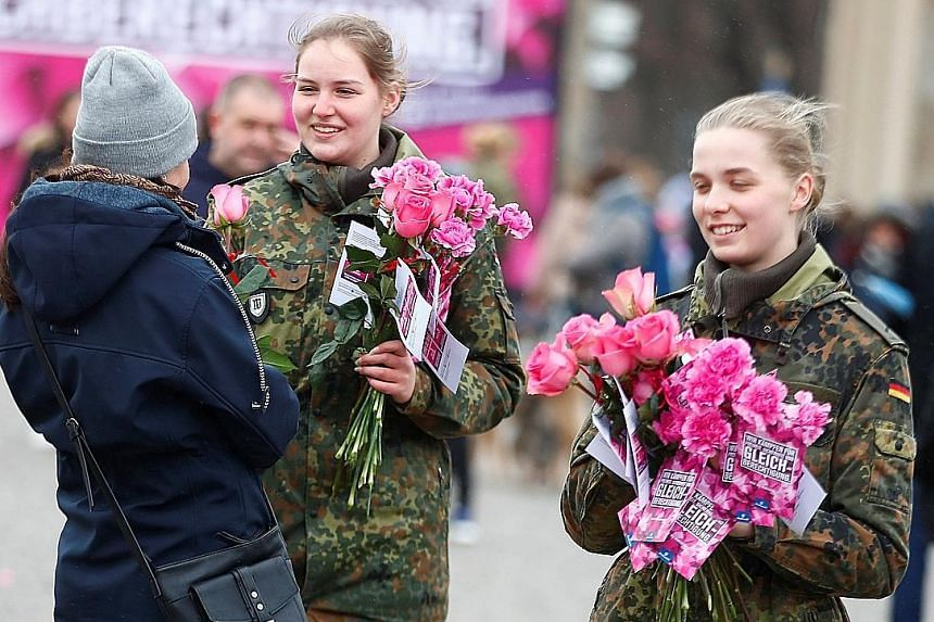 IN SOUTH KOREA: South Korean women dressed as witches with placards supporting feminism during a protest yesterday in Seoul. IN GERMANY: Female soldiers of the Bundeswehr, or German armed forces, giving out flowers to women near the Brandenburg Gate