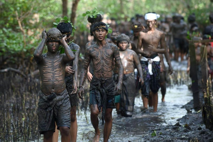 Balinese people put mud on their bodies during a traditional mud bath known as Mebuug-buugan, in Kedonganan village, on March 8, 2018.
