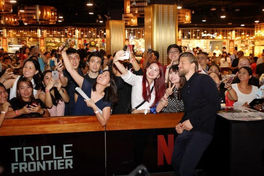 Triple Frontier star Charlie Hunnam taking pictures with fans at the Digital Light Canvas at The Shoppes at Marina Bay Sands on March 8, 2019.