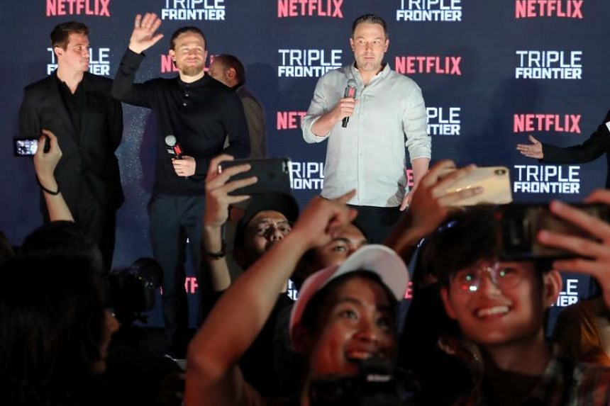 (From left) Triple Frontier stars Garrett Hedlund, Charlie Hunnam, Ben Affleck and along with Producer Chuck Roven (hidden), greet fans at the Digital Light Canvas at The Shoppes at Marina Bay Sands on March 8, 2019.