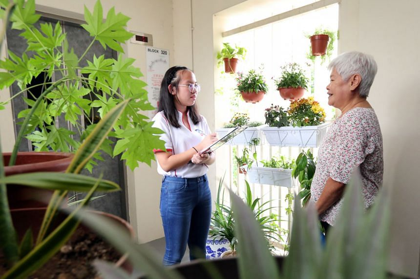 Neighbour Cares volunteer Marilyn Lim, a 16-year-old Nan Hua High School student, speaking to a fellow Yuhua resident during one of her weekly visits to check in on elderly residents in the neighbourhood.