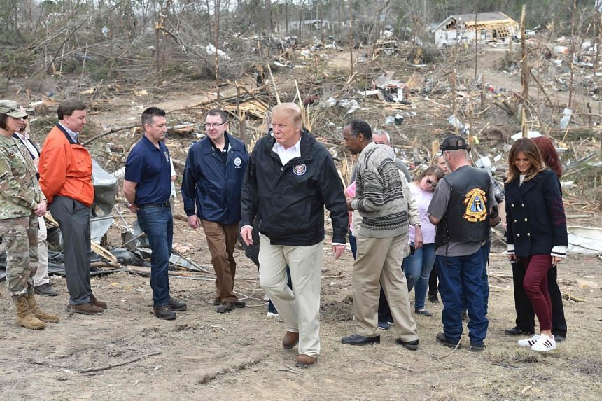 Trump (centre) tours the affected area with Melania Trump (right) and Ben Carson (centre-right), US Secretary of Housing and Urban Development.