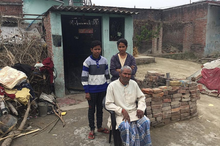 Mr Dhruvnarayan Sharma with his daughters Neha (left) and Jyoti (right) outside their house in Banwari Tola. A neurological disorder reduced mobility on 60-year-old Mr Sharma's right side, making him incapable of working at the modest barbershop he o