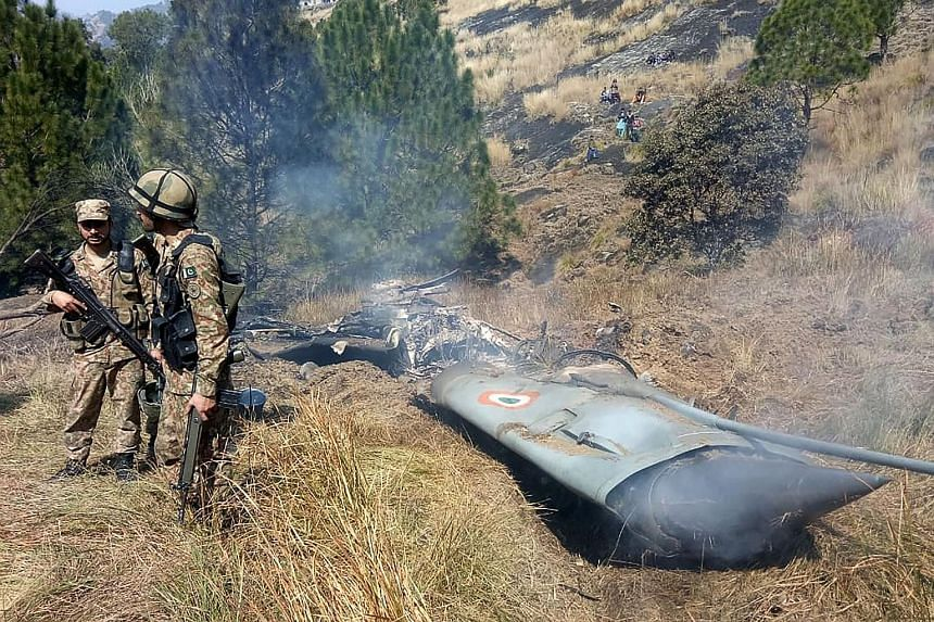 Top: Indian Armed Forces officials showing wreckage from an AIM-120 Advanced Medium-Range Air-to-Air Missile found in Indian territory, allegedly fired by a Pakistani F-16. Above: Pakistani soldiers standing next to what Islamabad claims is the wreck