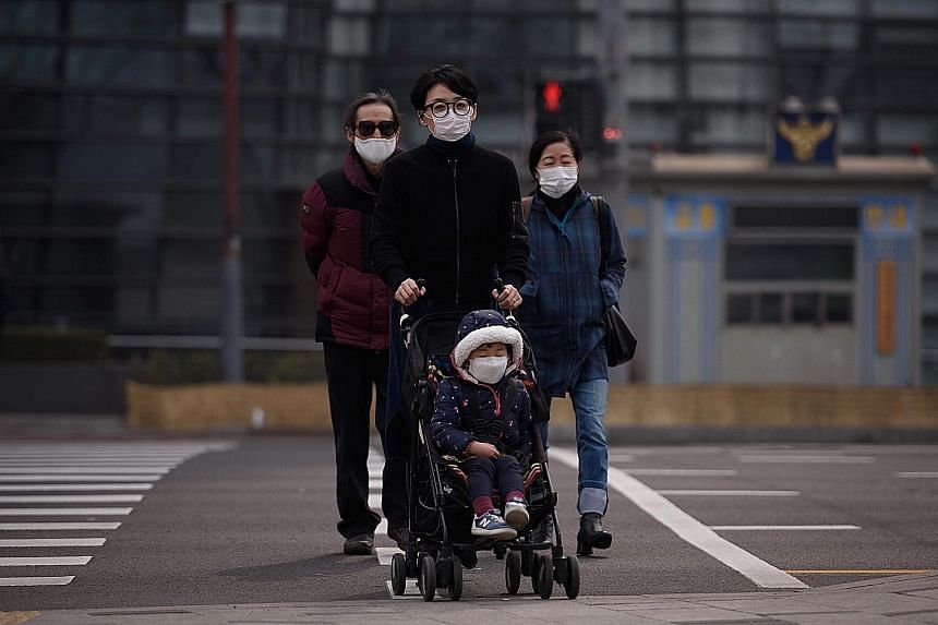 Masked policemen on guard outside the integrated government building in Seoul last Tuesday. A family taking precautions as they venture outside in Seoul. Anti-dust masks are flying off the shelves amid rising pollution. Apartment complexes in Seoul s