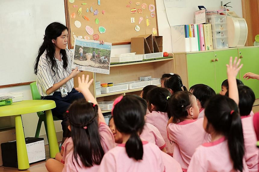 Teacher Chng Shu Min posing questions about the whale story published in The Straits Times as the children give their views on the subject.