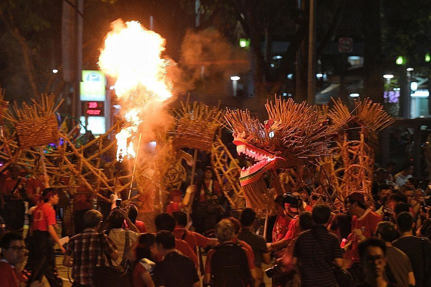 Members of the Mun San Fook Tuck Chee temple wielding a 60m-long dragon (left) made of straw and joss sticks (below) during the fire dragon dance held at the temple in Sims Drive last Friday. The dance is performed only once every three years and cel