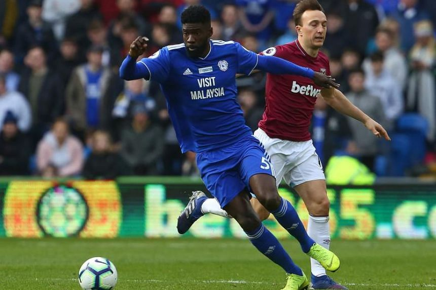 Cardiff City's Gabonese defender Bruno Ecuele Manga (left) vies with West Ham United's English midfielder Mark Noble during the EPL match between between Cardiff City and West Ham United at Cardiff City Stadium in Cardiff, south Wales on March 9, 201