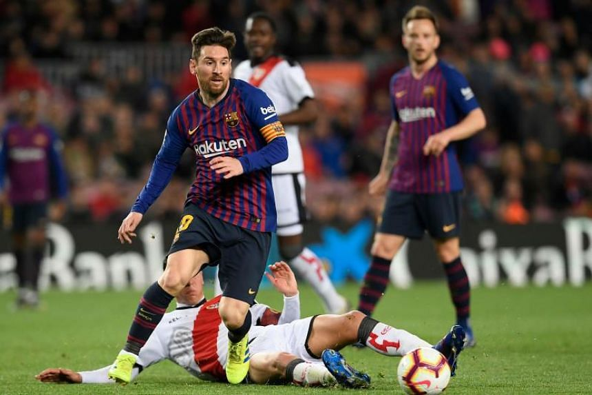 Barcelona's Lionel Messi vies for the ball with Rayo Vallecano's Santi Comesana during their La Liga match at the Nou Camp in Barcelona on March 9, 2019.