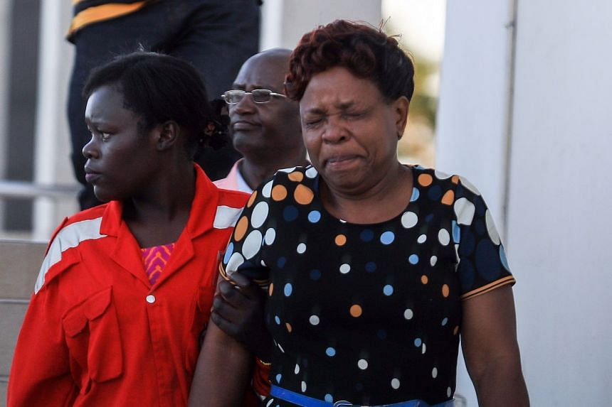 A Kenyan woman (right) is comforted by a Red Cross worker, after getting information about her loved ones.