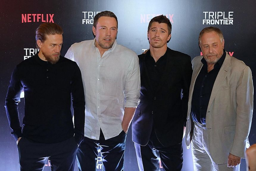 CHARLIE HUNNAM (far left, in Singapore with Triple Frontier stars Ben Affleck and Garrett Hedlund and producer Chuck Roven.