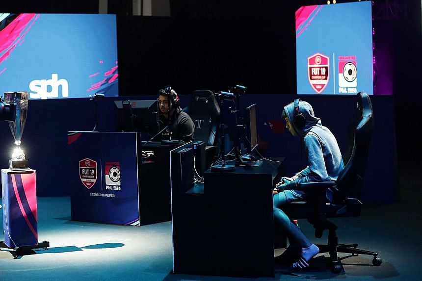 "Donovan ""F2Tekkz"" Hunt (above), 17, acknowledging the crowd's cheers after winning the Fifa Ultimate Team Champions Cup yesterday. During the grand final (below), both he and his rival Fatih ""M10Ustun"" Ustun banked on fast reflexes and intense concen"