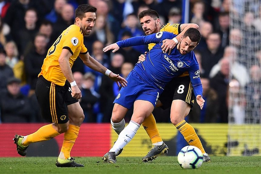 Chelsea forward Eden Hazard challenged by Wolves midfielders Ruben Neves (No. 8) and Joao Moutinho. The Belgian scored a last-gasp equaliser from outside the box at Stamford Bridge yesterday to salvage a 1-1 draw with Wolves. The visitors had taken t