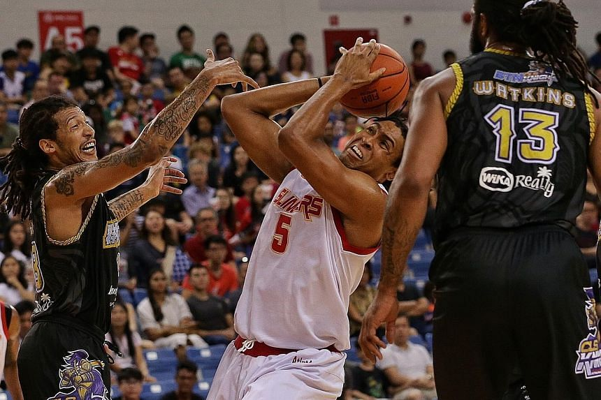 Singapore Slingers' John Fields trying to get past CLS Knights' Maxie Esho and Darryl Watkins in their Asean Basketball League game at the OCBC Arena. The visitors won 99-95.