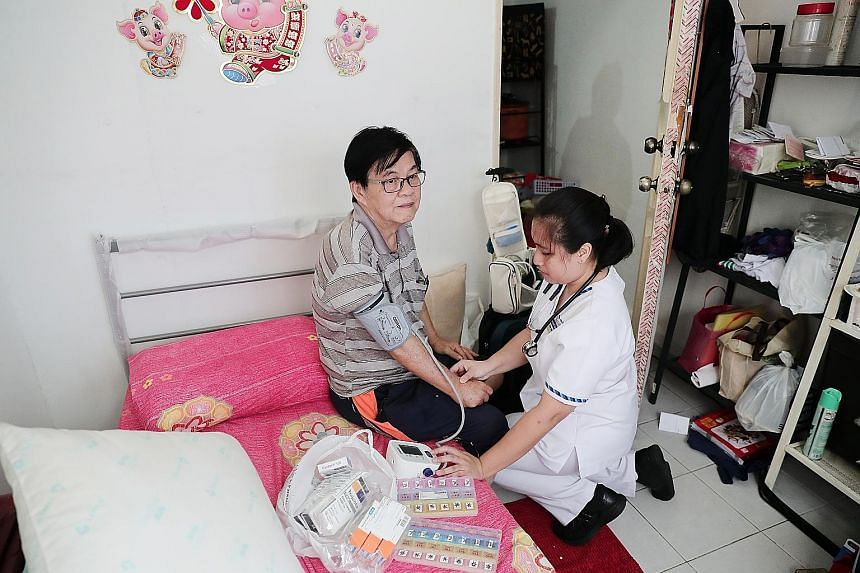 Retiree Lau Eng Boon, 65, getting his blood pressure checked by community nurse Murni Nadhirah Abdul Rahim, 30. She helped him to organise his pills for various conditions, including hypertension and stroke, into pill boxes to make it easier for him