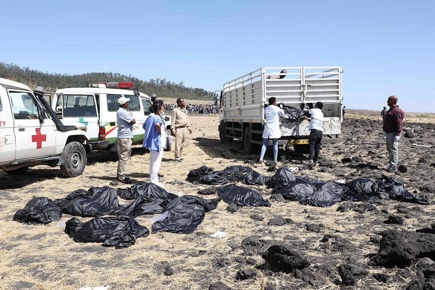 Emergency workers recovering the bodies of victims of the Nairobi-bound Ethiopian Airlines flight at the crash site near Bishoftu, 62km south-east of Addis Ababa, yesterday. There were no survivors. The plane was carrying 149 passengers and eight cre